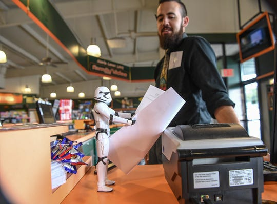 Family Video manager James Werner looks at a Star Wars stormtrooper holding a list of movies that he placed near his computer. The store celebrated its 10th anniversary earlier this year.