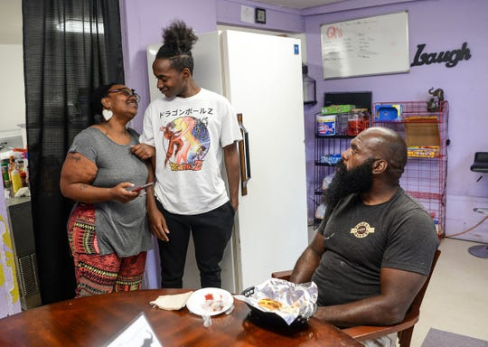 Tiyonneteona Davis, left, owner of KrisTee's Hot Dog's in Anderson, hugs her son Christopher Davis, middle, after bringing a hot dog to customer Bernard Simmons of Anderson.