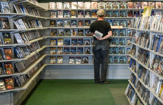 Reggie Titmas peruses the selections. For many video store shoppers, browing the shelves is part of the appeal.