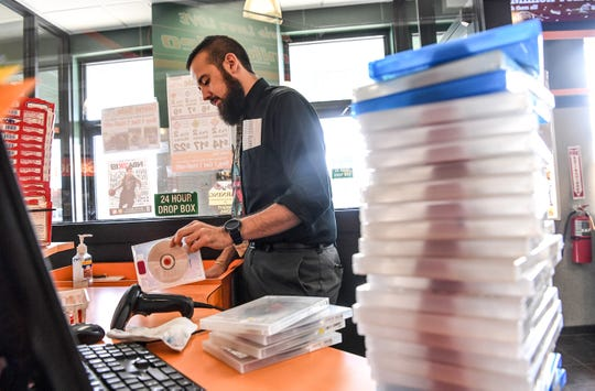 Manager James Werner looks over movies that have been returned to Family Video.