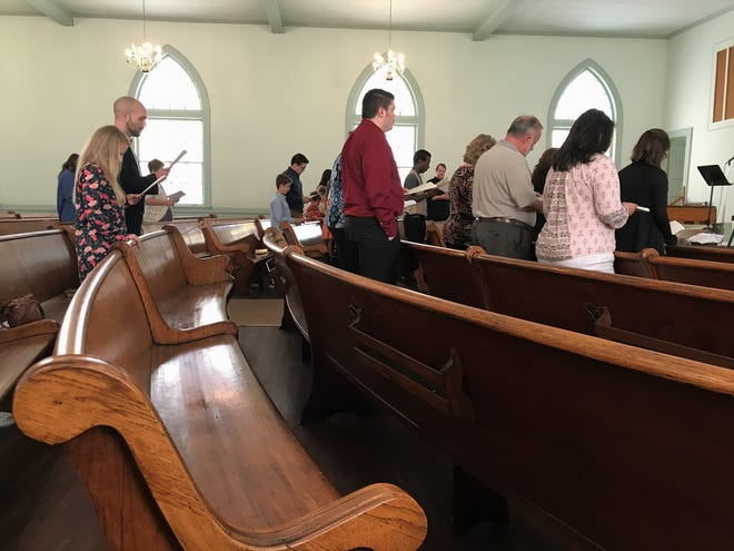 Curved pews with carvings that can be felt on the back are the centerpiece of the century-old building now being used by Christ the Redeemer - Greenville.
