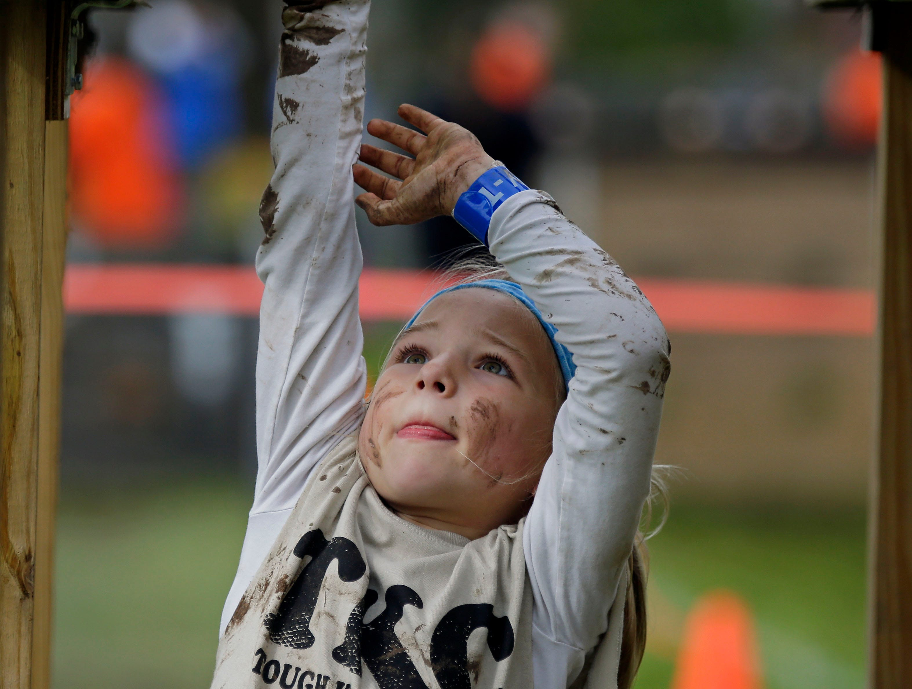 Vanessa Lewis of Greenville concentrates on crossing the monkey bars as the Essity Fox Valley Tough Kid Challenge takes place Saturday, October 6, 2018, at Highlands Elementary School in Appleton, Wis. The event raised funds for Physical Education Departments in Appleton.