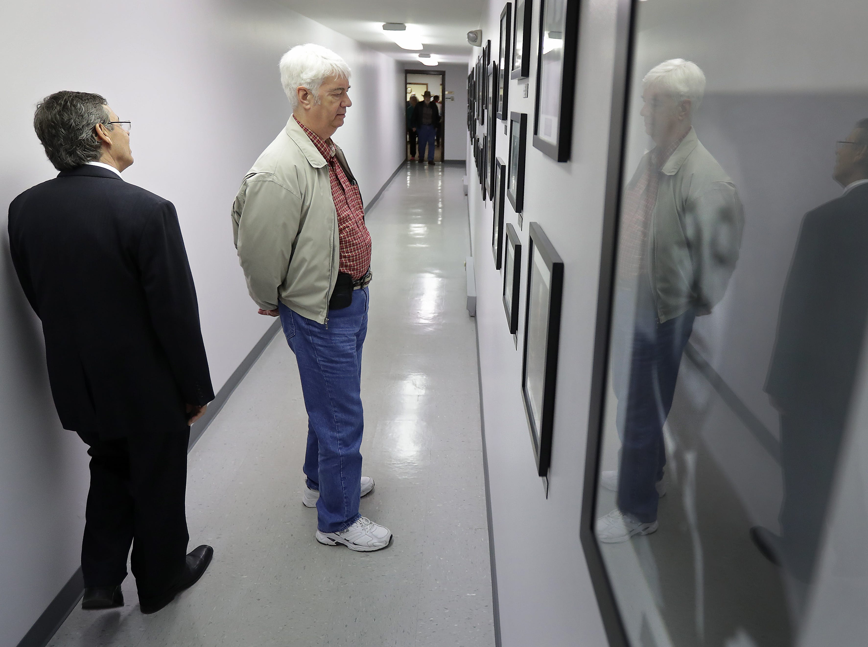 Regional field director Wayne morrow, left and Ivan Price, on right from North Carolina, look at photos in the Robert Welch Hall during the John Birch Society 60th anniversary open house at the John Birch Society headquarters building and The New American news magazine building on Westhill Blvd. on Friday, October 5, 2018, in Grand Chute, Wis. 