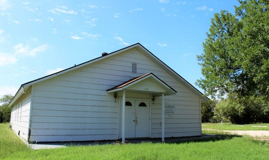 A church building that also served as a funeral home stands alone on North 12th Street.
