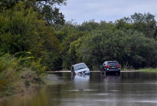 Two cars stand in receding floodwaters on Marigold Street near Little Elm Creek on the north side of Abilene Tuesday.