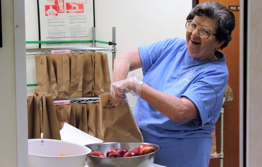 A volunteer bags lunches to go before 7 a.m. at Breakfast on Beech Street, a free-meal program that has operated out of First Christian Church downtown. The church is moving but the program will continue.