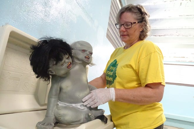 Betsy Gerhart places a two-headed baby on a diaper-changing station Tuesday inside the poolhouse at Aumiller Park.