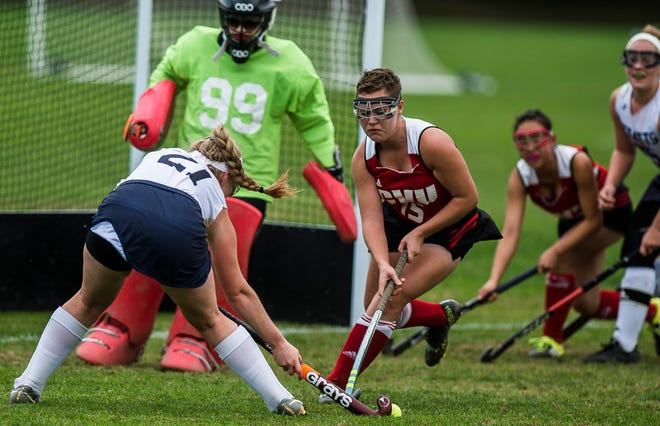 Essex #21 Sarah Coulter tries to get a shot off as CVU #15 Nora Weisman-Rowell comes in to block during their high school field hockey game at Essex High School on Monday, Oct. 8. 2018. Essex won, 2-1.