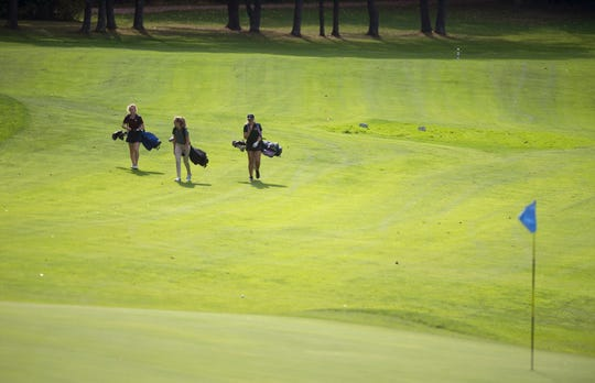 Golfers walk up the 11th fairway during the 2018 high school girls golf state championships at Ralph Myhre Golf Course in Middlebury on Tuesday.
