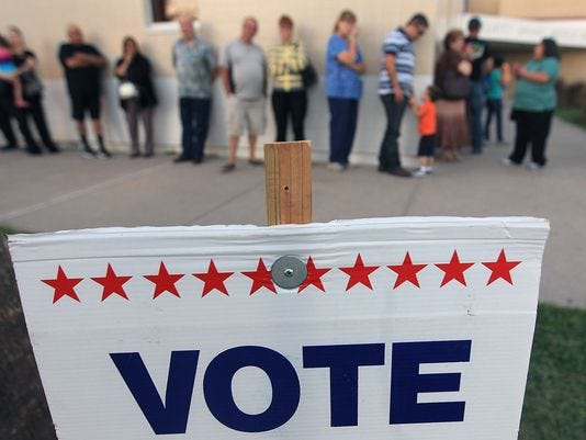 In this 2012 file photo, a line of voters snakes around the outside of a polling location at Grant Middle School.