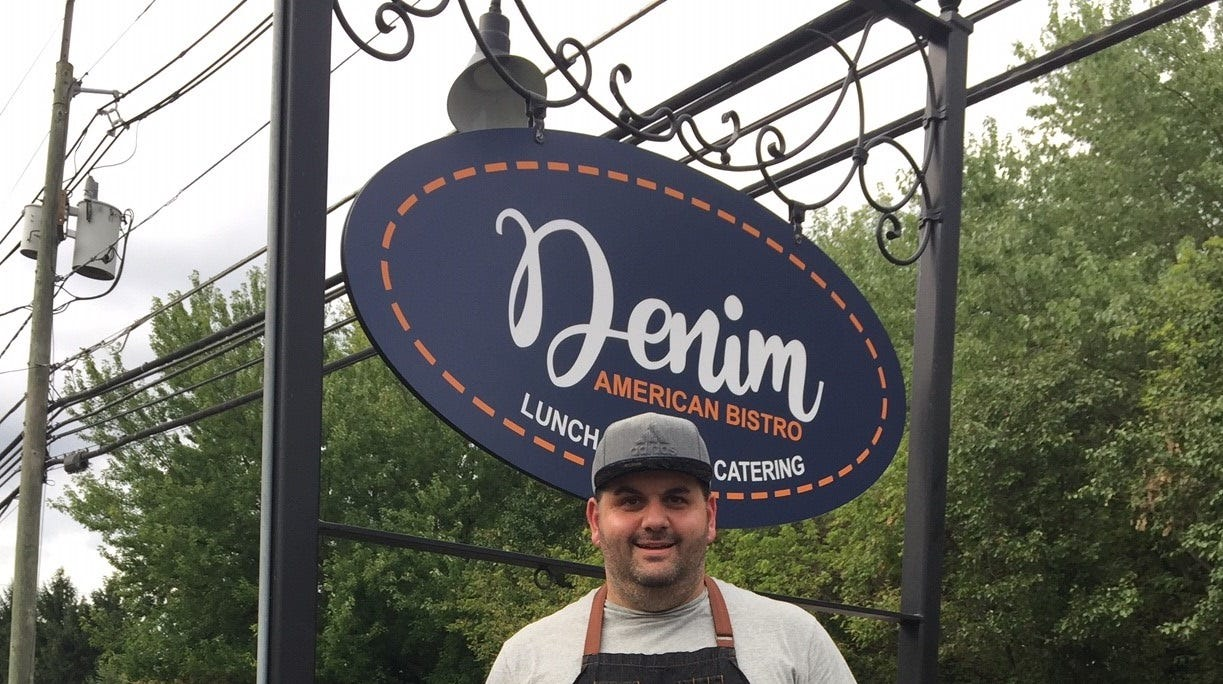 Chef-owner David Murray, sporting a denim apron, stands near the sign to his new restaurant, Denim American Bistro in Cherry Hill. He hopes to open the doors as early as Friday, pending final inspections.
