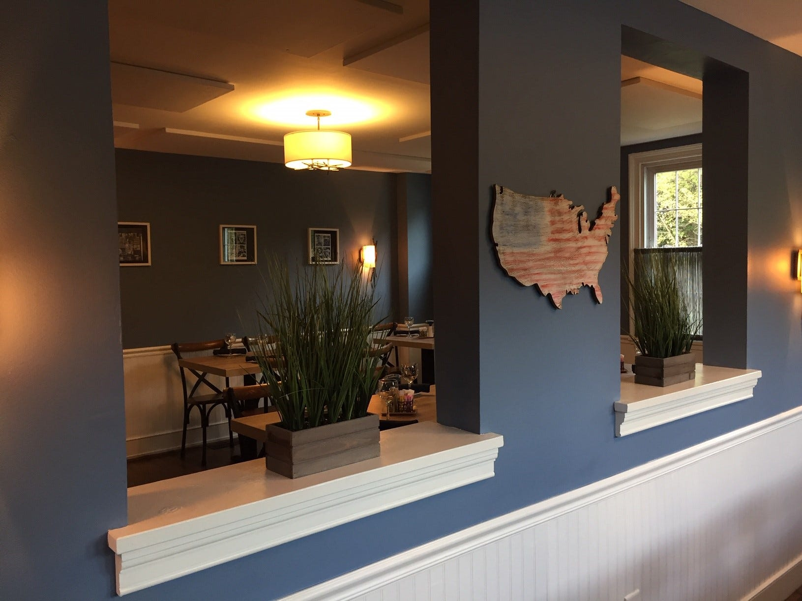 An interior window provides a look at a second dining area at Denim American Bistro in Cherry Hill.