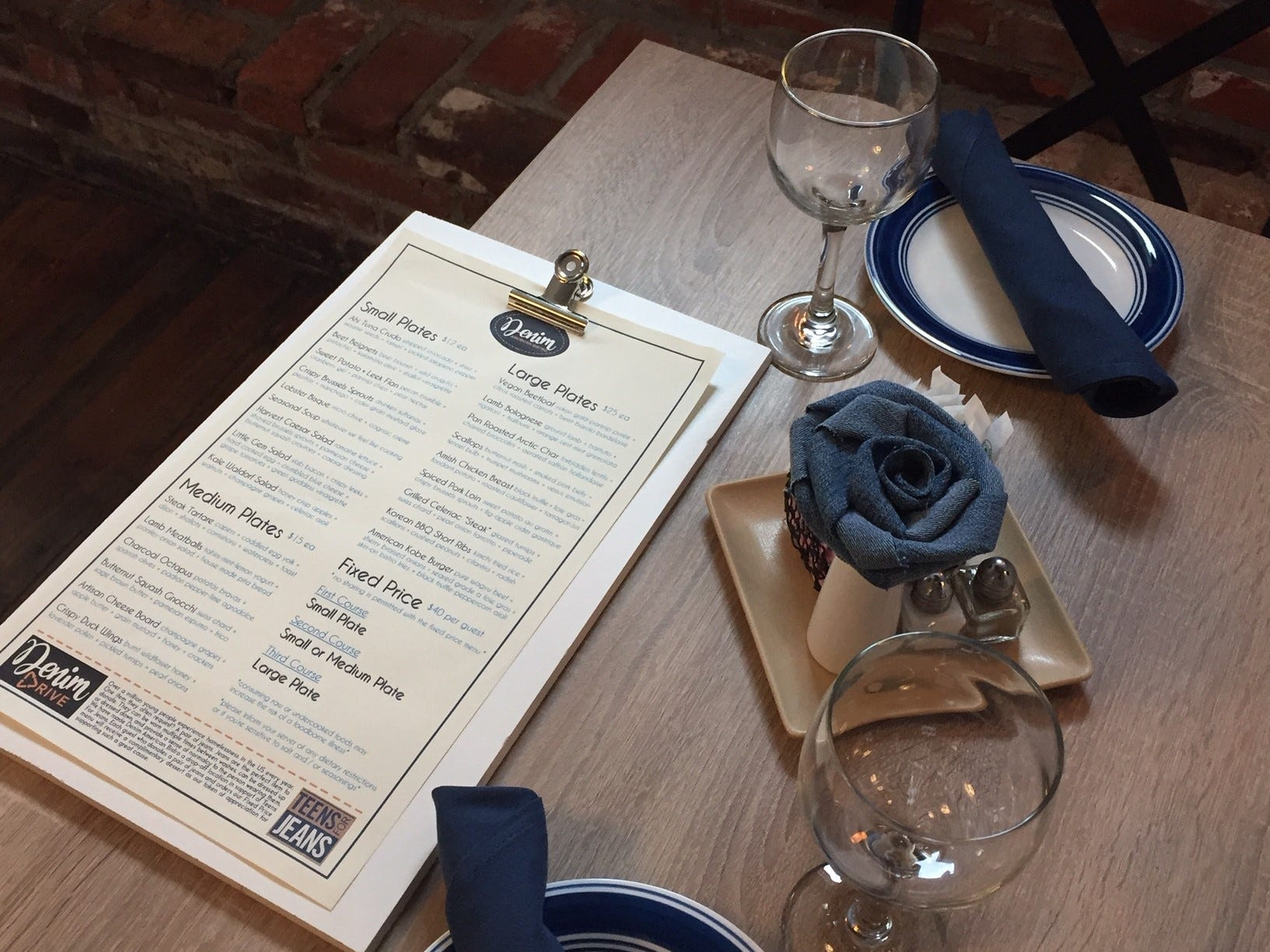 "A Denim American Bistro Menu awaits guests at a table for two. The dinner menu will feature ""new interpretations of  American classics,'' Murray says."