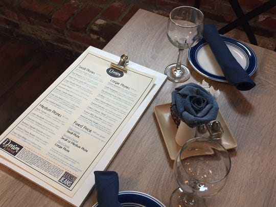 """A Denim American Bistro Menu awaits guests at a table for two. The dinner menu will feature """"new interpretations of  American classics,'' Murray says."""
