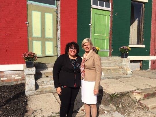 Seven Hills Neighborhood Houses' Tia Brown, Left, and Laura Brunner of The Port stand outside row houses planned  for redevelopment in the West End.
