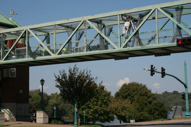 Workers from Pride Concrete LLC work Monday on the Riverside Drive Pedestrian Overpass. The painting project, which will require some lane changes, is expected to begin Oct. 15.