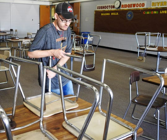 Jalen Berry puts chairs on table at the Coshocton County Career Center, part of his average work day along with cleaning tables and washing dishes.
