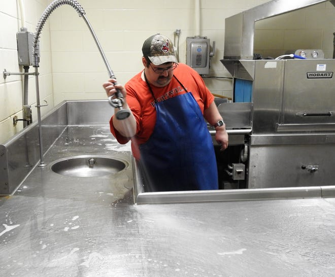 Brandon Corder sprays down the sink area in the dish room of the Coshocton County Career Center at the end of his shift. Corder was a student at the school before taking a job there in 2015.