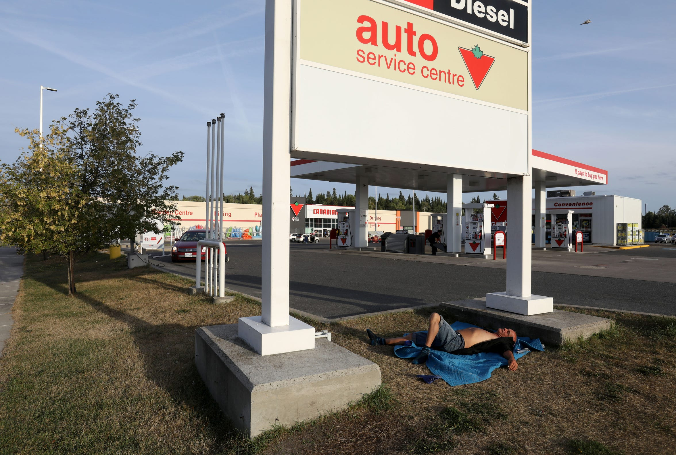 Joe Murphy takes a nap underneath the Canadian Tire gas station sign in Kenora, Ontario, Canada.