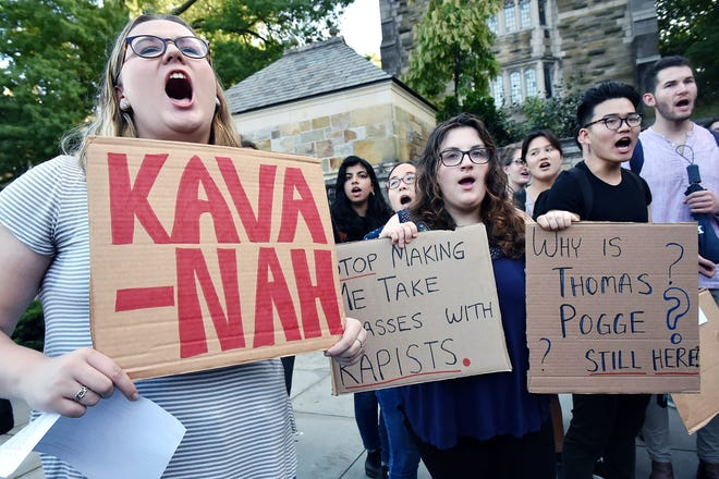 Yale University students Maryanne Cosgrove, Anna Blech, and Douglas Shao, attend a rally at the Women's Table on campus in New Haven, Conn., Wednesday, Sept. 26, 2018, protesting the nomination of Brett Kavanaugh to the Supreme Court due to allegations of sexual misconduct. Kavanaugh graduated from Yale in 1987 with a Bachelor of Arts and Yale Law School in 1990. (Catherine Avalone/New Haven Register via AP)