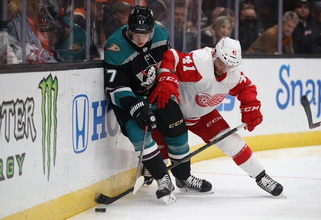 Luke Glendening of the Detroit Red Wings defends Rickard Rakell of the Anaheim Ducks during the first period Monday, Oct. 8, 2018, in Anaheim, Calif.