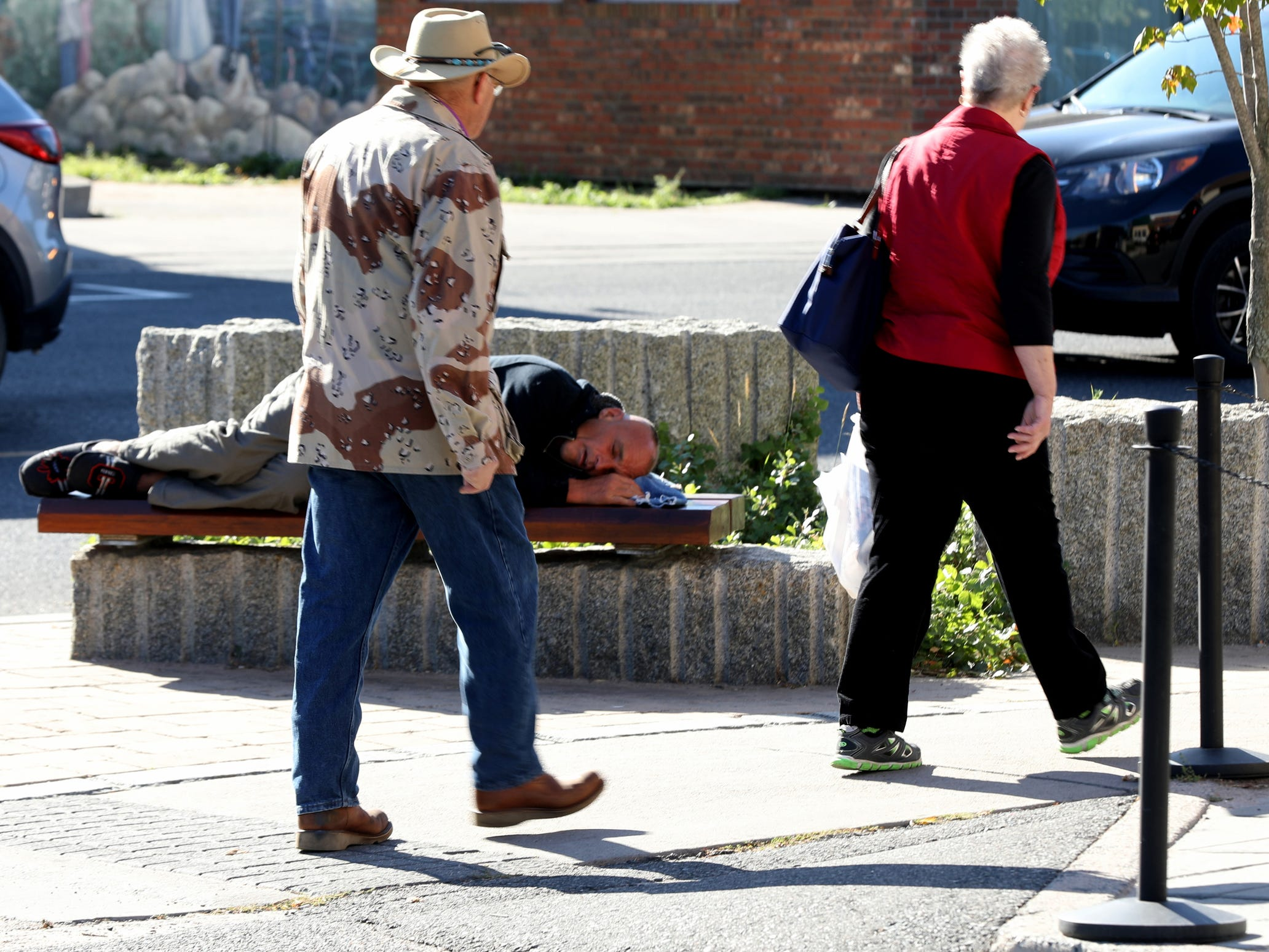 People walk by as Joe Murphy takes a nap on a wooden bench the heart of downtown Kenora, Ontario, Canada.