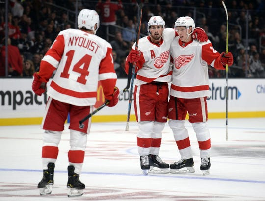 Detroit Red Wings center Dylan Larkin, middle, celebrates a goal with center Michael Rasmussen, right, and right wing Gustav Nyquist against the Los Angeles Kings in the third period at Staples Center, Oct. 7, 2018.