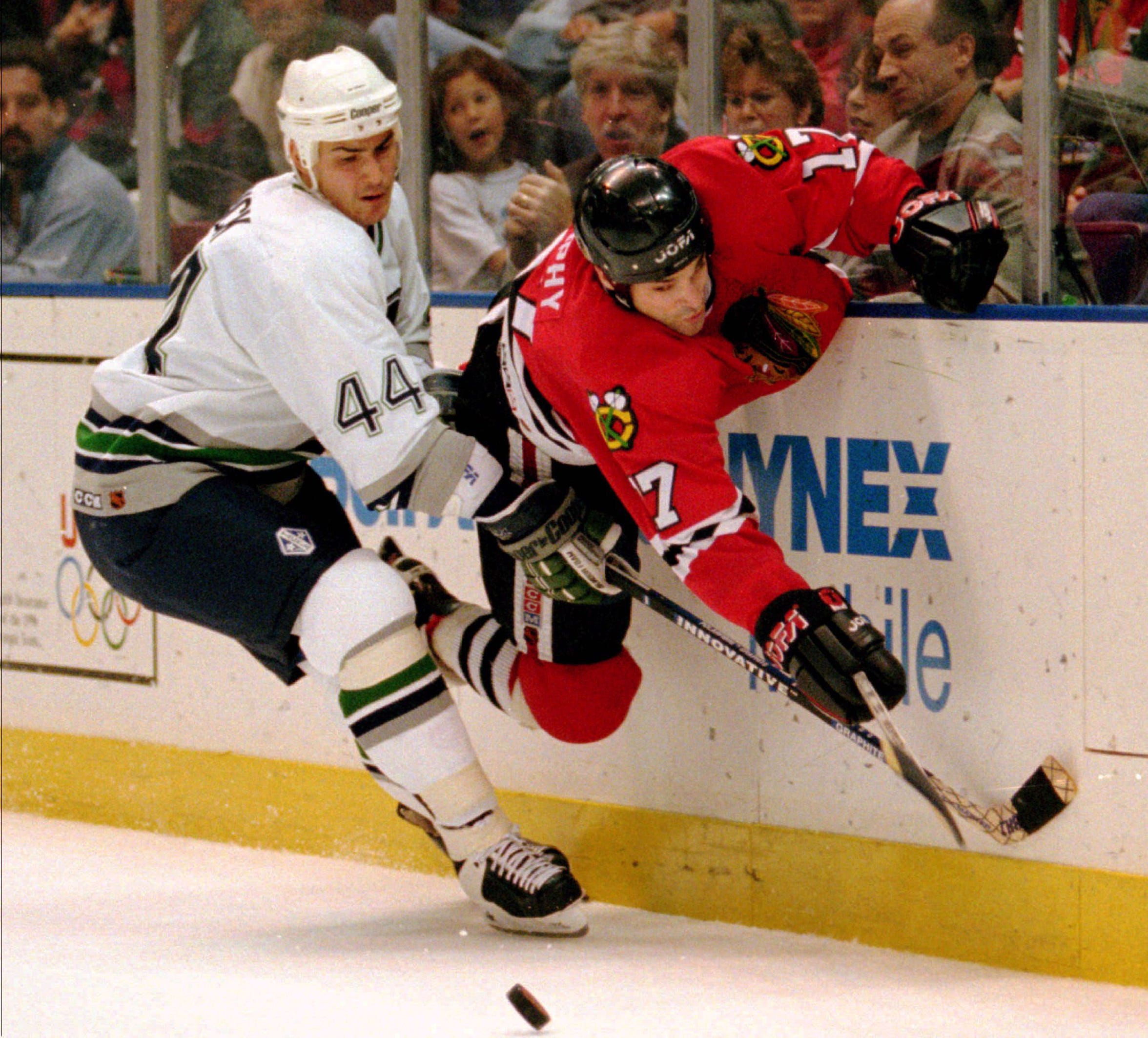 Chicago Blackhawks winger Joe Murphy, right, goes flying against the boards as he fights for the puck with Hartford Whalers defenseman Gerald Diduck (44) behind the Whalers' net during first-period action at the Hartford Civic Center, Saturday, Oct. 14, 1995. (AP Photo/Richard Mei)