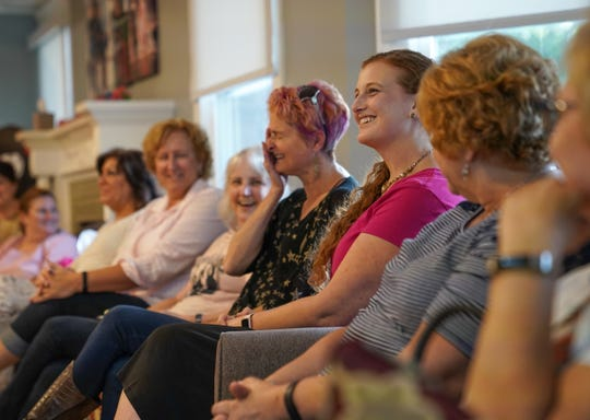 Heather Jablonowski (center right) of Berkley laughs with other breast cancer survivors on Thursday, Oct. 4, 2018, at Gilda's Club in Royal Oak while introducing herself before a walk-through and rehearsal for this year's Bras for a Cause event.
