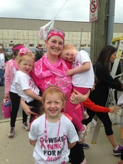 "Breast cancer survivor Heather Jablonowski of Berkley holds her twin daughters, Audrey (left) and Ashlyn. Her older daughter, Charlotte, stands in front of them. The girls all wore shirts that said, ""I wear pink for my mom"" while attending the Pink Out the Park event at Comerica Park in 2015."