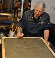 Mickey Lolich writes his name after casting his hands in cement for the Detroit Historical Museum's Legends Plaza on Saturday, Oct. 6, 2018.