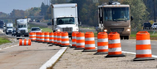 Traffic on westbound I-96 makes its way past orange construction barrels near Ionia, Michigan on Tuesday.