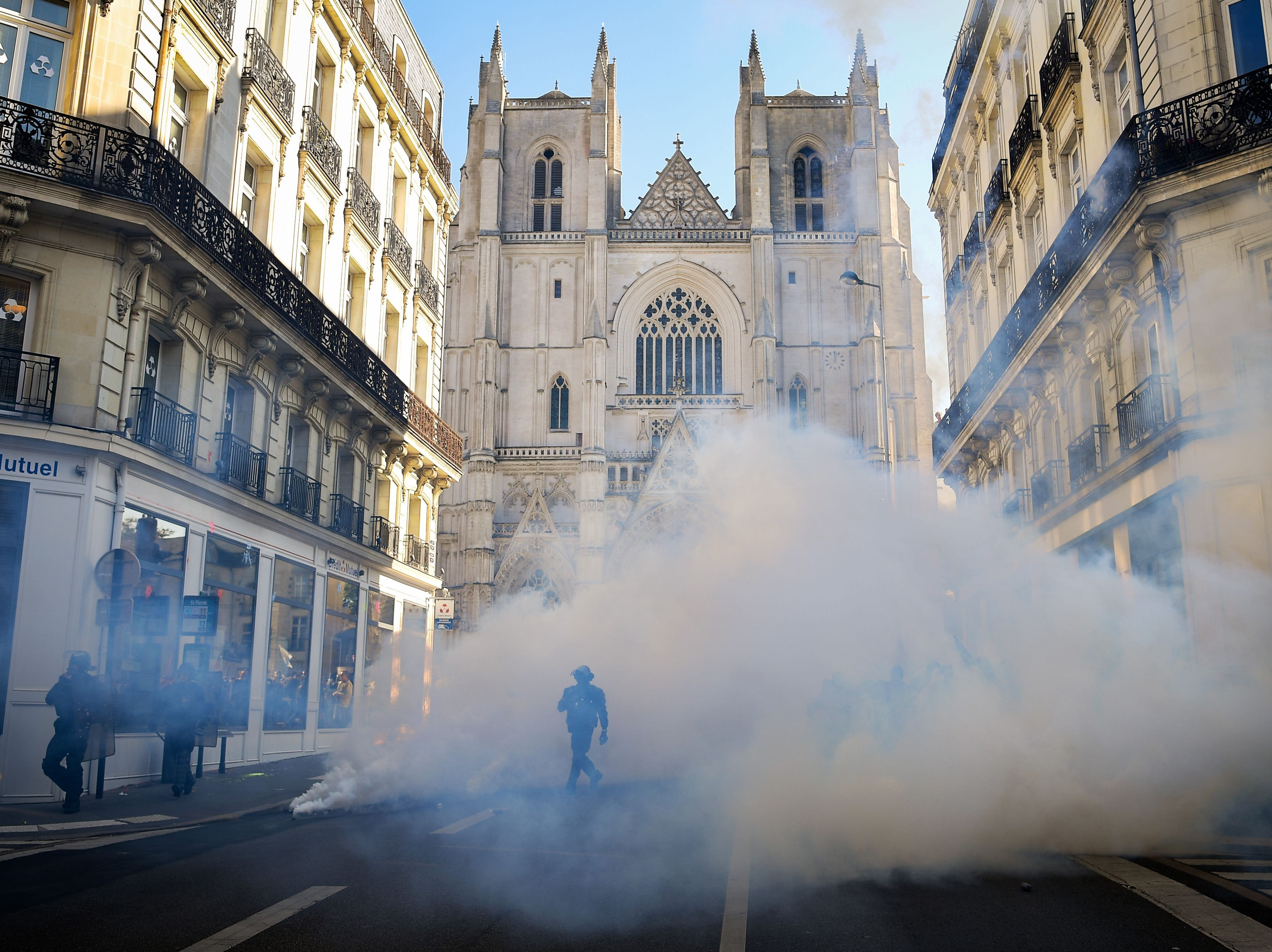 Anti-riot police charge protesters Tuesday during a one-day nationwide strike over President Emmanuel Macron's policies in Nantes, France.