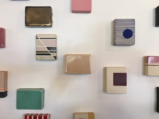 """A small sampling of the handsome, glazed tablets in Elysia Vandenbussche's """"Stay,"""" which cover the wall behind the Trumbull & Porter check-in counter."""