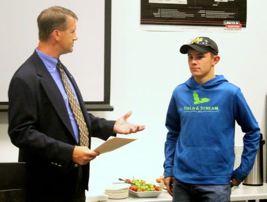 Cameron Manufacturing and Design President and CEO Chris Goll, left, presents a welding scholarship to Corning Community College student Chris Rocchi of Pine City.