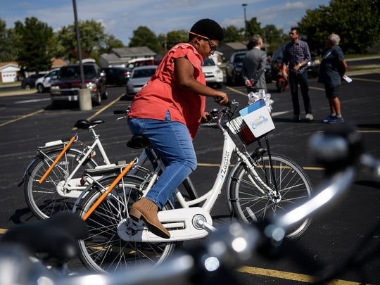 Faith Griffin, an Ivy Tech student, prepares to take a bicycle for a short spin around the parking lot at the new Evansville Trails Coalition Upgrade bike share location on the corner of Colonial Avenue and First Avenue, located beside the Ivy Tech campus in Evansville, Tuesday afternoon.