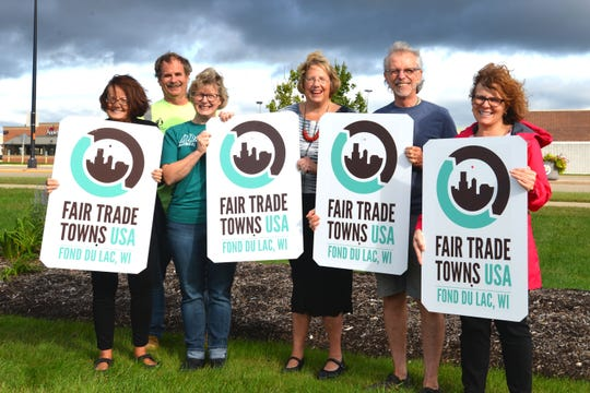 Fair Trade Towns USA signs are posted at the city's four main entrances. Pictured representing Fair Trade Towns Fond du Lac are, from left: Jane Braun, Village Market; Kevin Westphal, City of Fond du Lac; Anne Lemke, Moraine Park Technical College; Julia Cartwright, Just Fare Market; Howie Zanto, Living Light Studio; and Julie Balson, Gallery and Frame Shop.