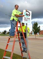 Kevin Westphal, left, and James Zahn,   right, of City of Fond du Lac Engineering post a Fair Trade Towns USA sign on West Johnson Street.