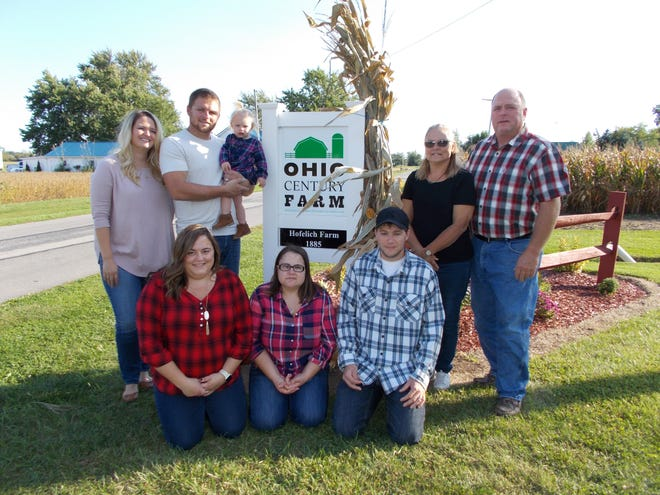 Matt and Tami Hofelich and family stand with the Century Farm sign awarded by the state.