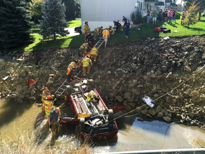 An unidentified man is slid up an embankment on a backboard after he was injured Tuesday afternoon when his car rolled down and overturned into Sucker Run Creek near W. Maple Street just west of Race Street.