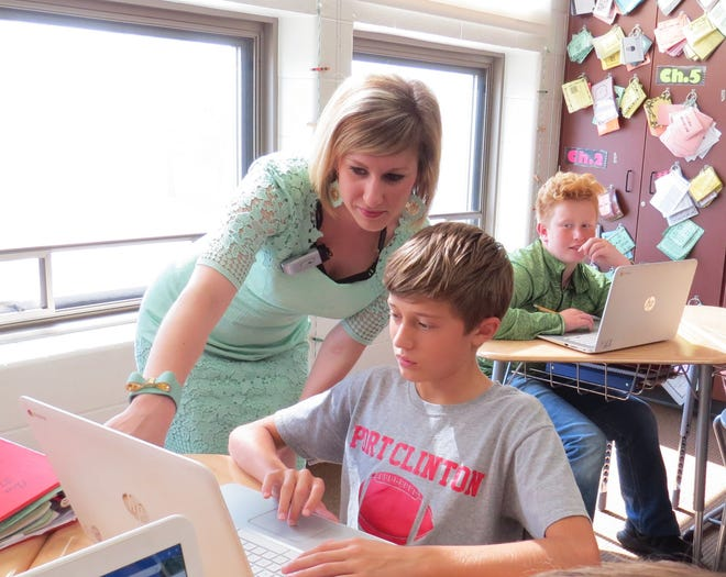 Port Clinton Middle School Mathematics teacher Sarah Moore stands by student Bert Fall.  Moore is being recognized by the Ohio Council of Teachers of Mathematics.