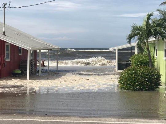 Water levels rise toward the street at Blind Pass on Sanibel Island. Storm surge as a result of Hurricane Michael is affecting Southwest Florida shorelines.