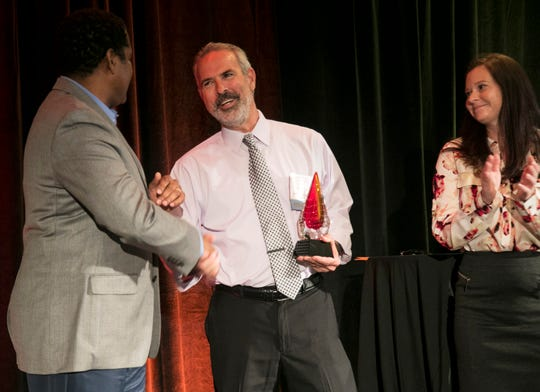 Michael Chatman of the Cape Coral Community Foundation congratulates Mark Blust of Watch D.O.G.S. after he won the Community Impact Award at the Excellence in Nonprofit Performance Yearly Awards on Tuesday, October 9, 2018, in Fort Myers.