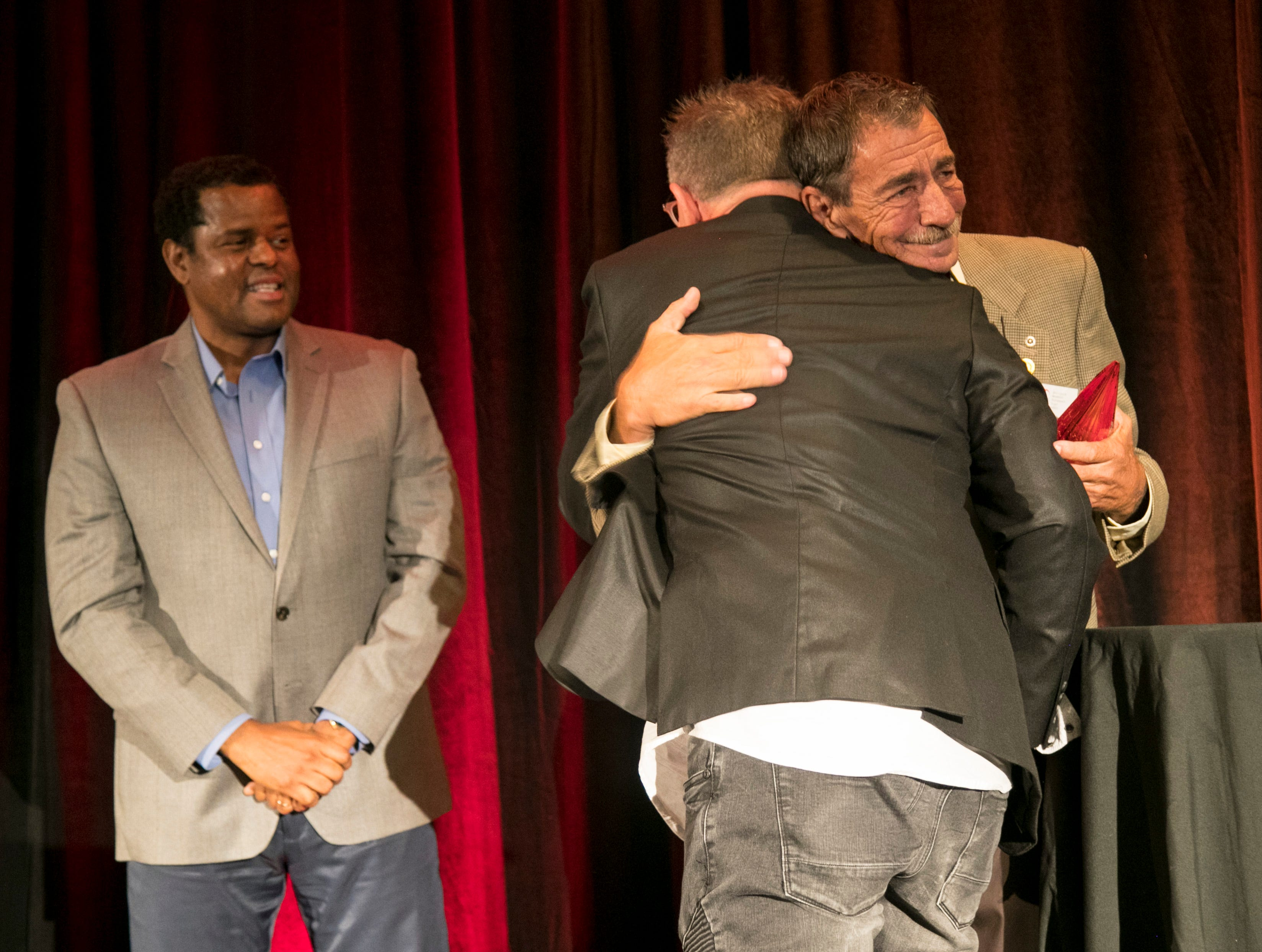 Elmer Tabor, right, hugs Dennis Gingerich, center, after Ginegrich won the 2018 Elmer Tabor Generosity Award at the Excellence in Nonprofit Performance Yearly Awards on Tuesday, October 9, 2018, in Fort Myers.