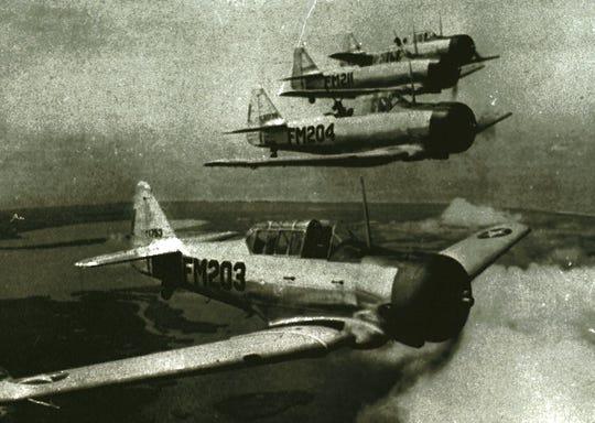 Historical photo of World War II era planes flying near Buckingham Army Air Field.