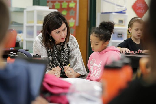 Third-grade teacher Erin Aschenbrenner works with Lila Arthur during class at Howe Elementary Community School on Friday in Green Bay.