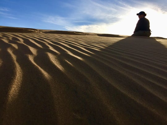 Stephanie Cutts in contemplation in the desert of Namibia.
