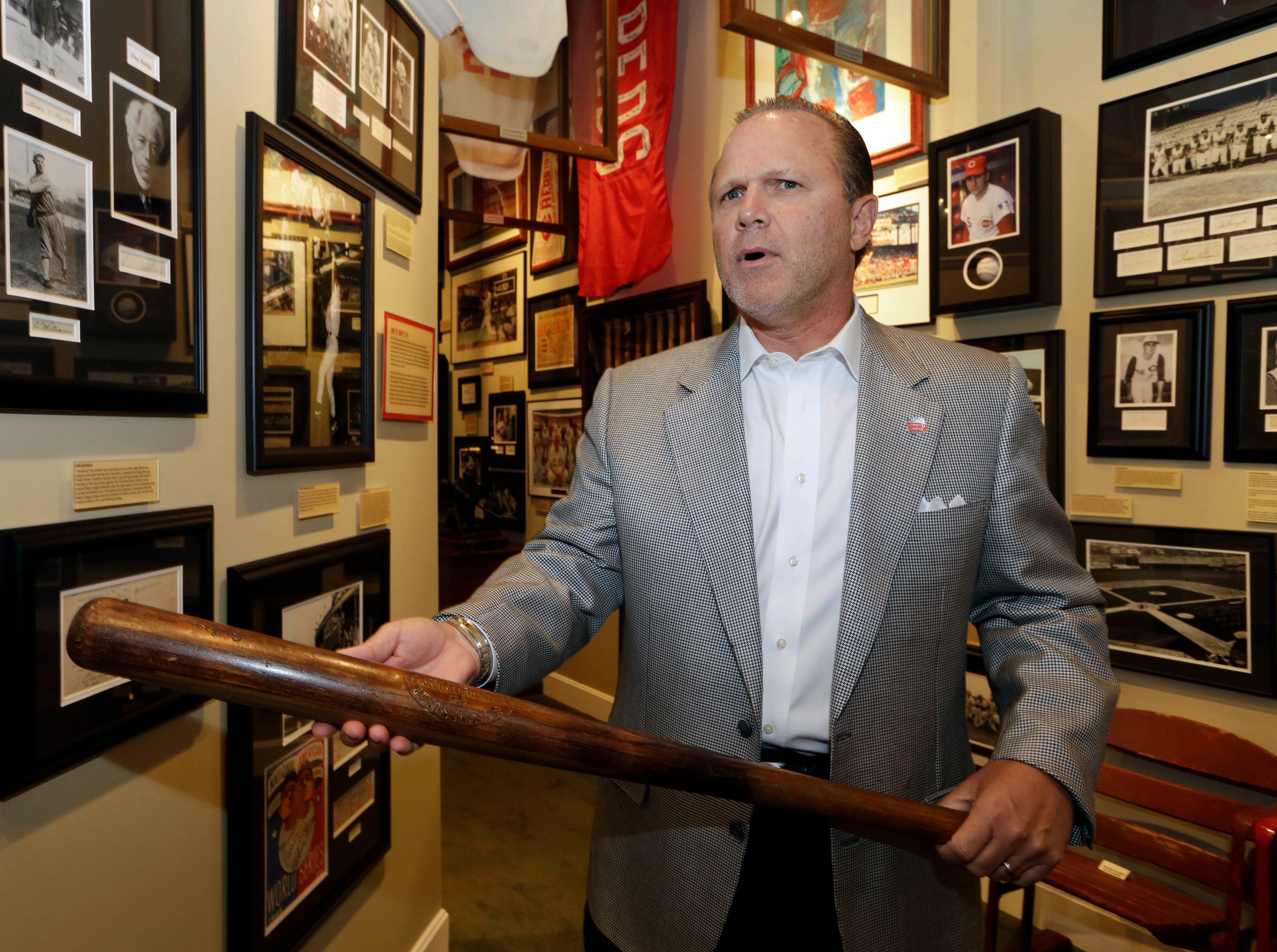Owner Bob Crotty holds a bat used by Shoeless Joe Jackson as he stands next to a display on the 1919 Chicago White Sox scandal, Tuesday, July 23, 2013, inside the Green Diamond Gallery in Cincinnati. The club houses baseball memorabilia and allows members to hear inside stories from the game's greats in monthly meetings. (AP Photo/Al Behrman)