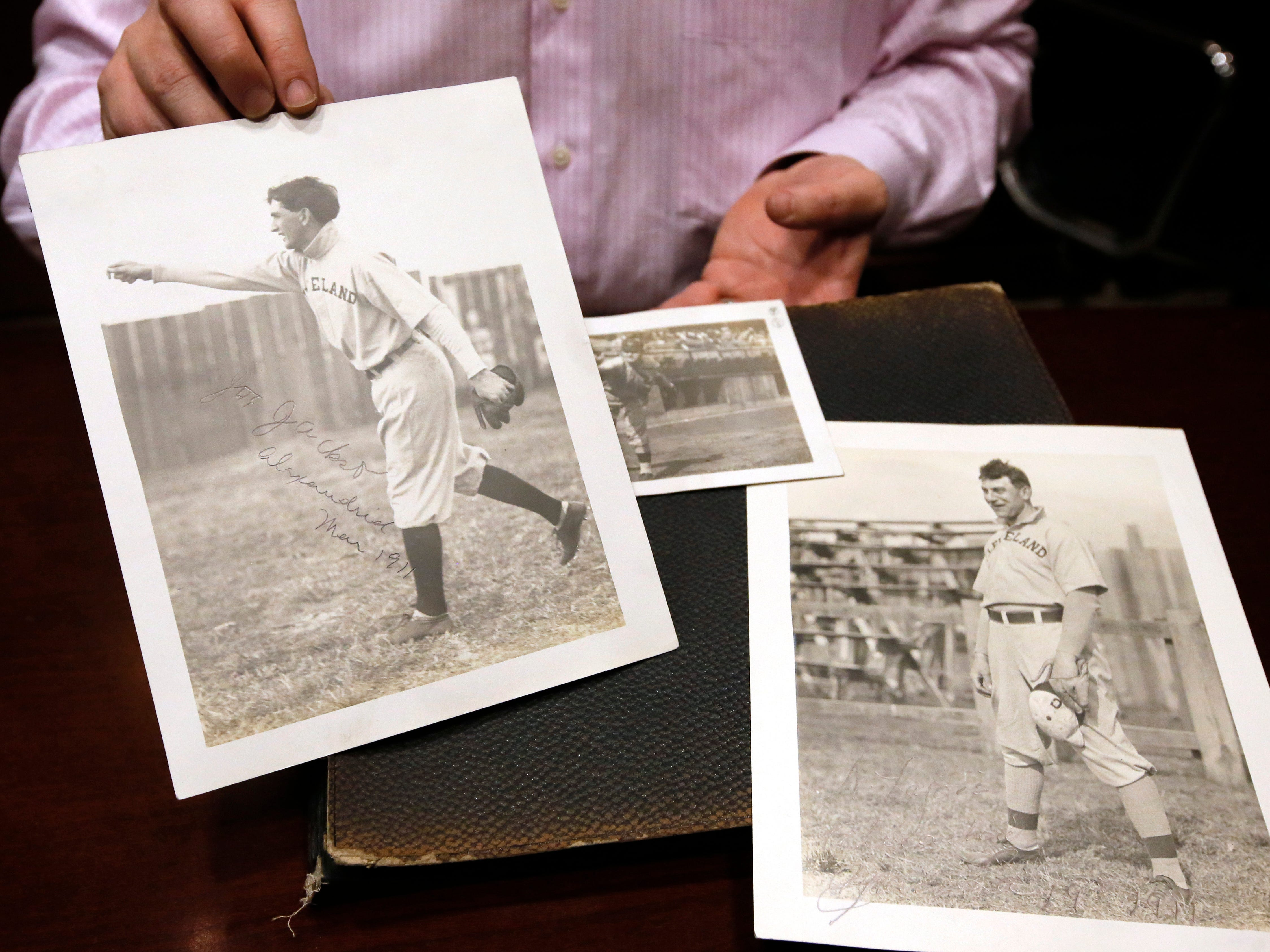 In this Jan. 22, 2015, photo, Chris Ivy, director of sports auctions at Heritage Auctions in Dallas, holds autographed photos of Cleveland ballplayers Joe Jackson, left, Christy Mathewson, center, and Nap Lajoie, right. Sharon Bowen thought her late husband was a bit crazy for buying a scrapbook with a bunch of black and white photos of Cleveland ballplayers from the early 1900s, but not anymore. It turns out that scrapbook held what may be the only autographed photo of Shoeless Joe Jackson. (AP Photo/Tony Gutierrez)