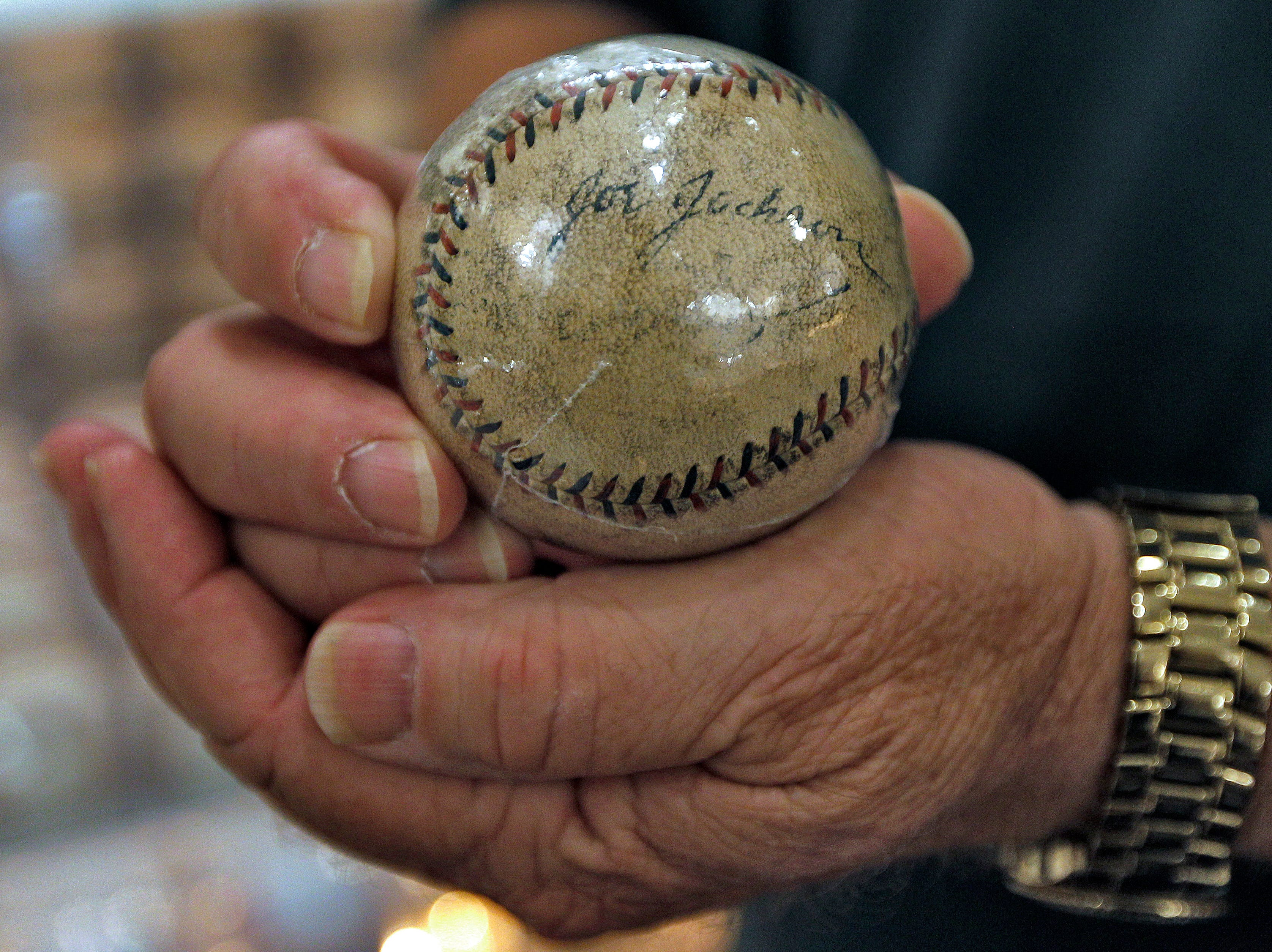 "In this Tuesday Sept. 27, 2011 photo, Dennis Schrader holds a 'Shoeless Joe"" Jackson autographed baseball at his home in Odessa, Fla. (AP Photo/Chris O'Meara)"